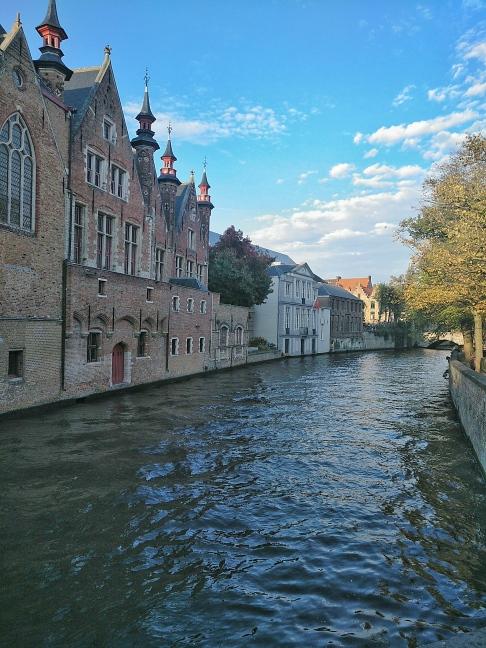 canal da cidade de bruges com casas na margem e arvores