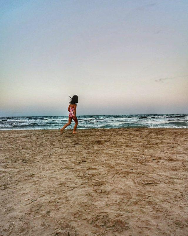criança correndo na areia da praia